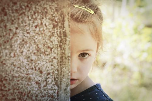 Kind hinter Säule